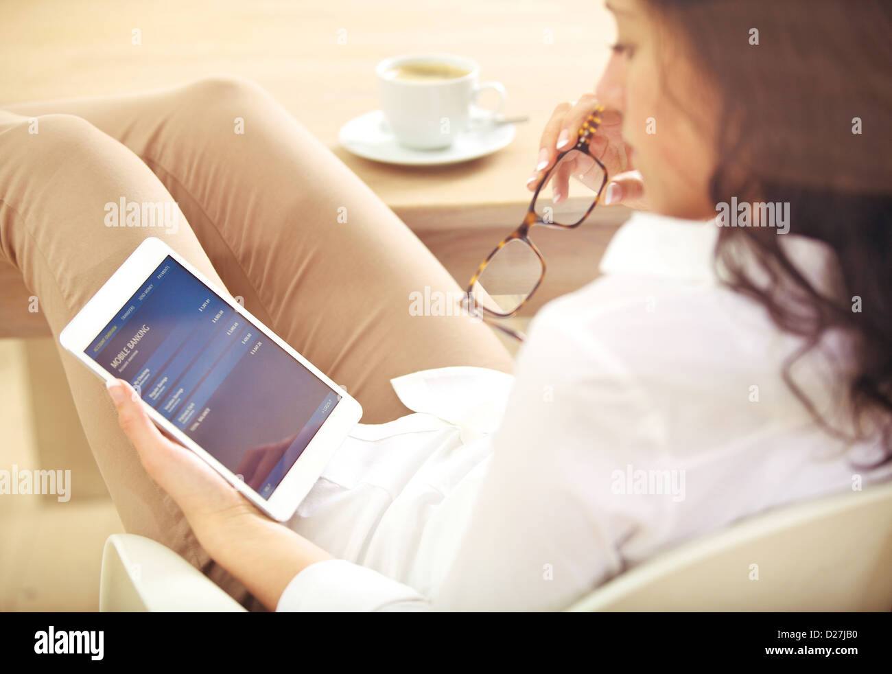 Young corporate woman checking information about her bank account online - Stock Image