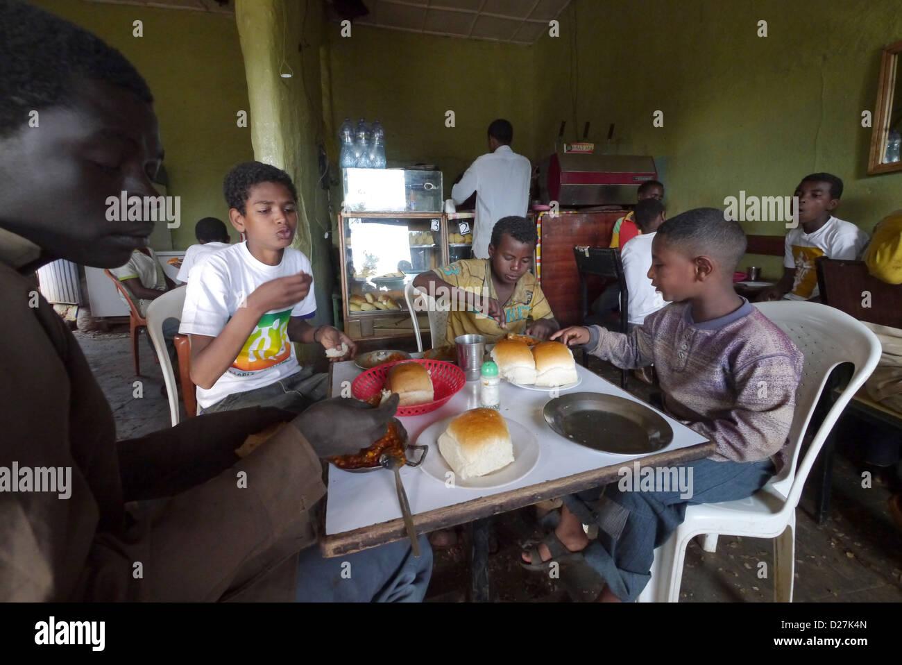 ETHIOPIA The 'Salam Cafe' in Chagni, Beni Shangul Gumuz region. Boys having breakfast of beans. Stock Photo