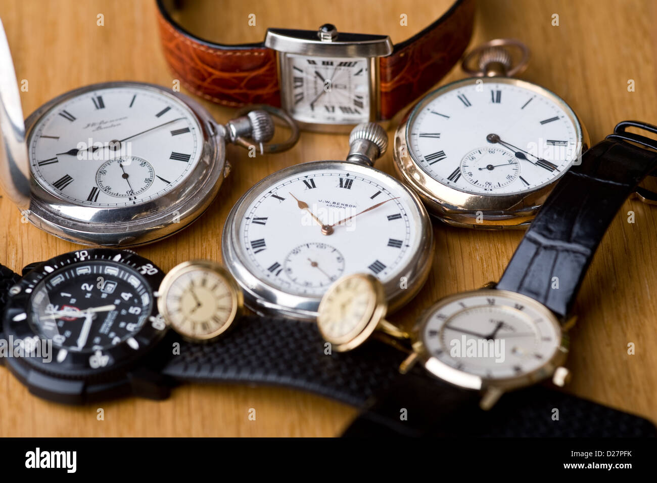 Group of pocket watches and wristwatches, on an oak table top. - Stock Image