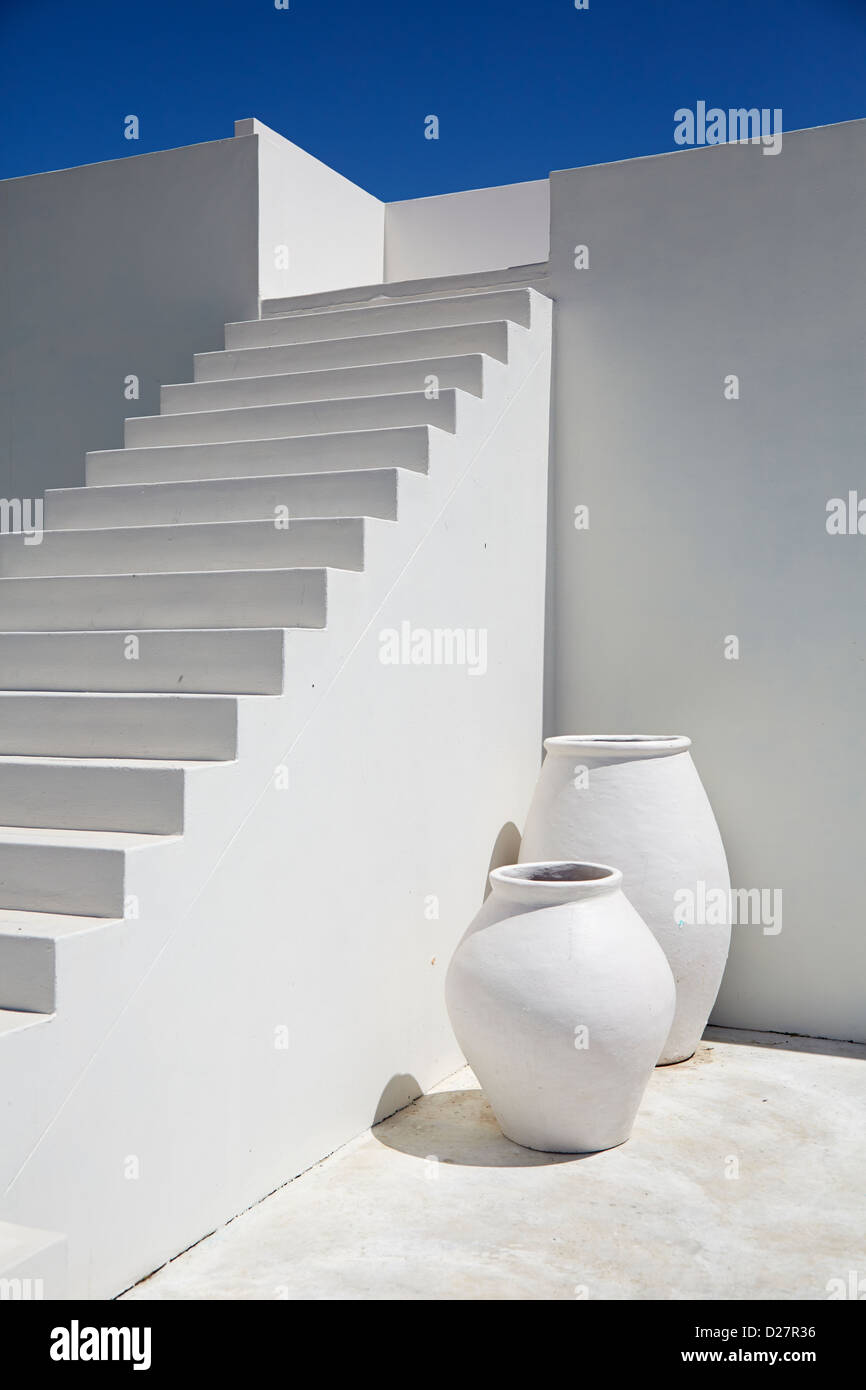 White stone stair case with walls and vases against a blue sky - Stock Image