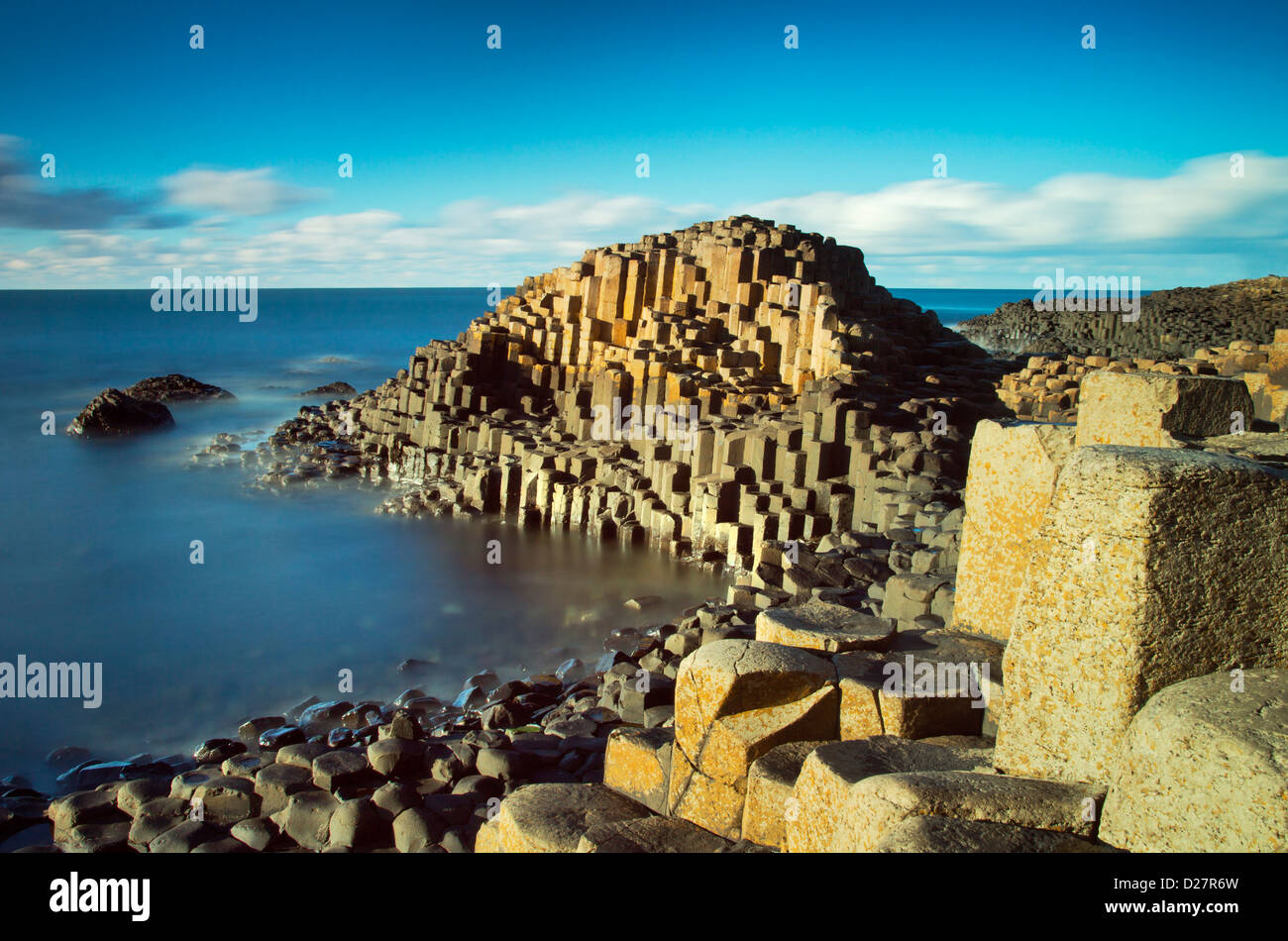 Sunny afternoon and calm waters on the famous Giant's Causeway on the Antrim Coast of Northern Ireland - Stock Image