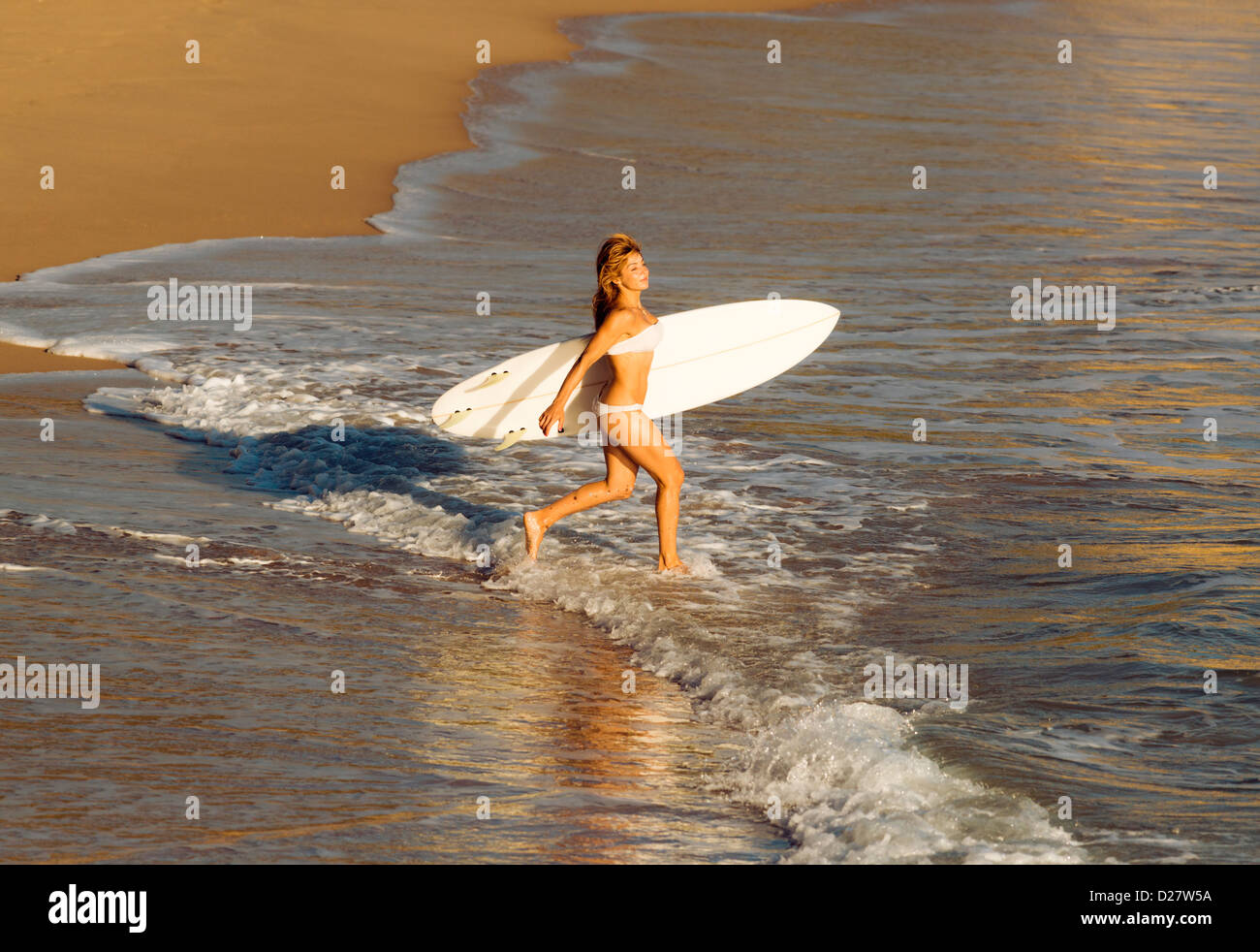 Woman going into the sea with her surf board. - Stock Image