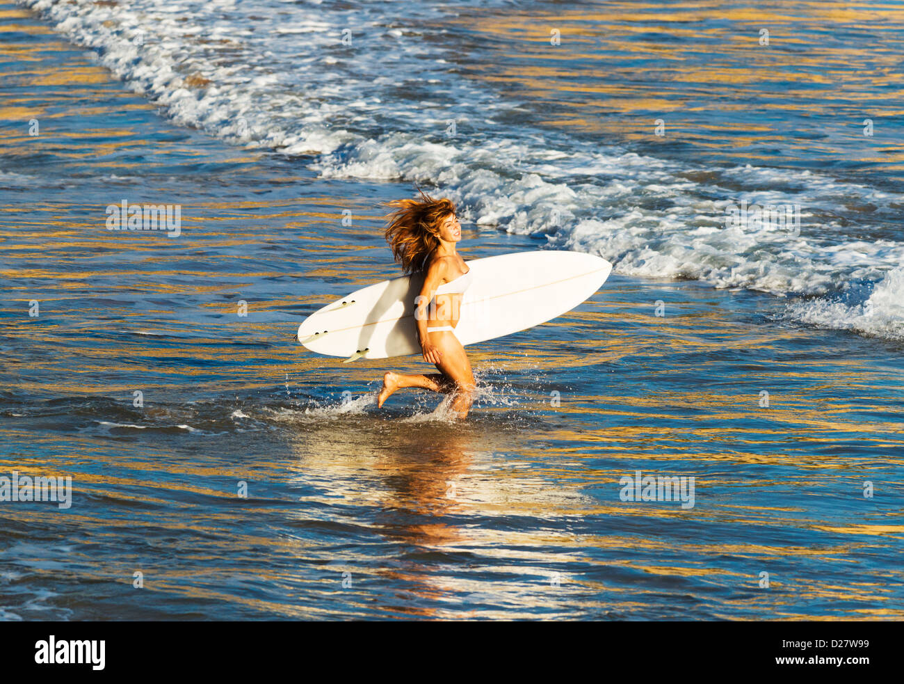 Woman running in the water. - Stock Image