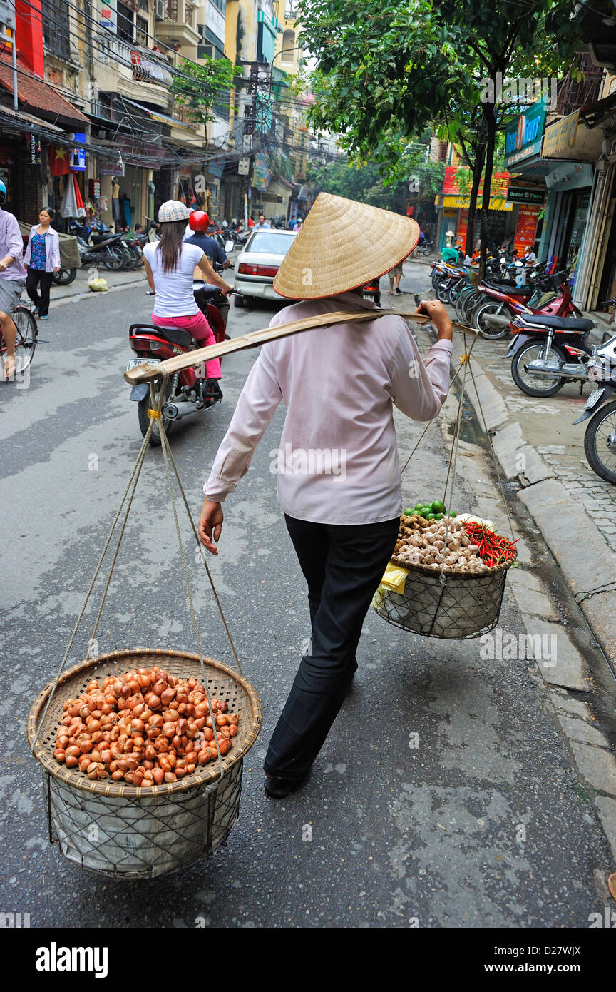 Hanoi, Vietnam - Woman carrying baskets on fruits with people street scene - Stock Image
