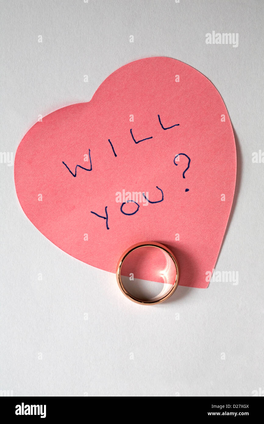 Will you? written on pink heart shaped post it note with wedding ring - marriage proposal isolated on white background - Stock Image