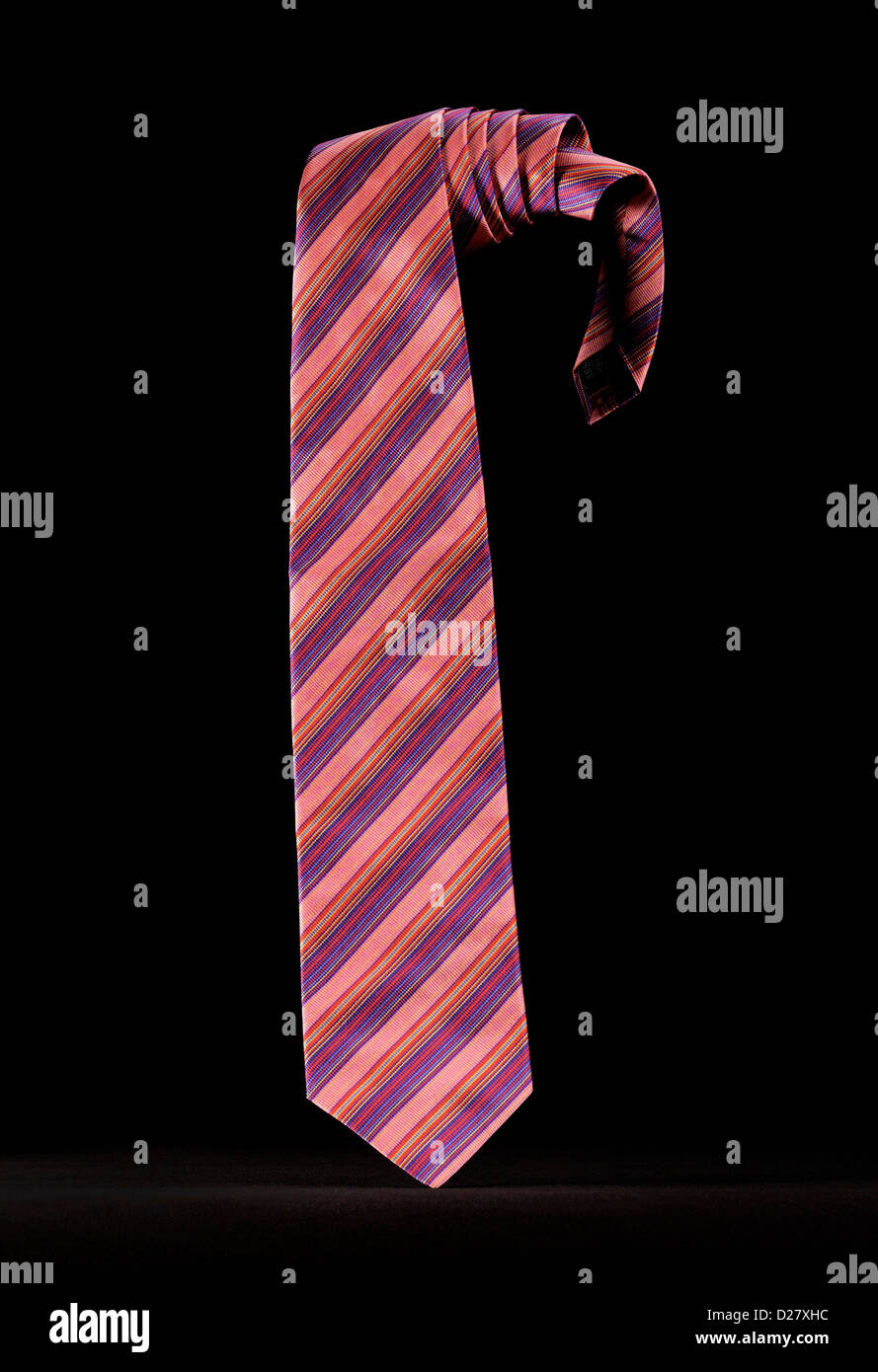 Pink and Purple Striped necktie on Black Background - Stock Image