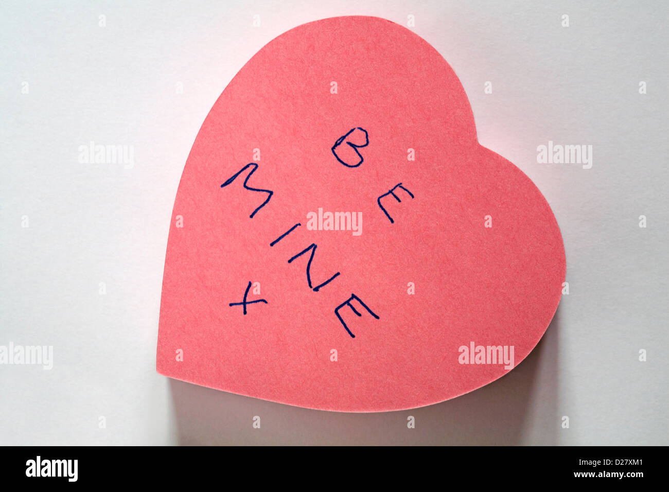 Be mine x message written on pink heart shaped post it note pad isolated on white background Stock Photo