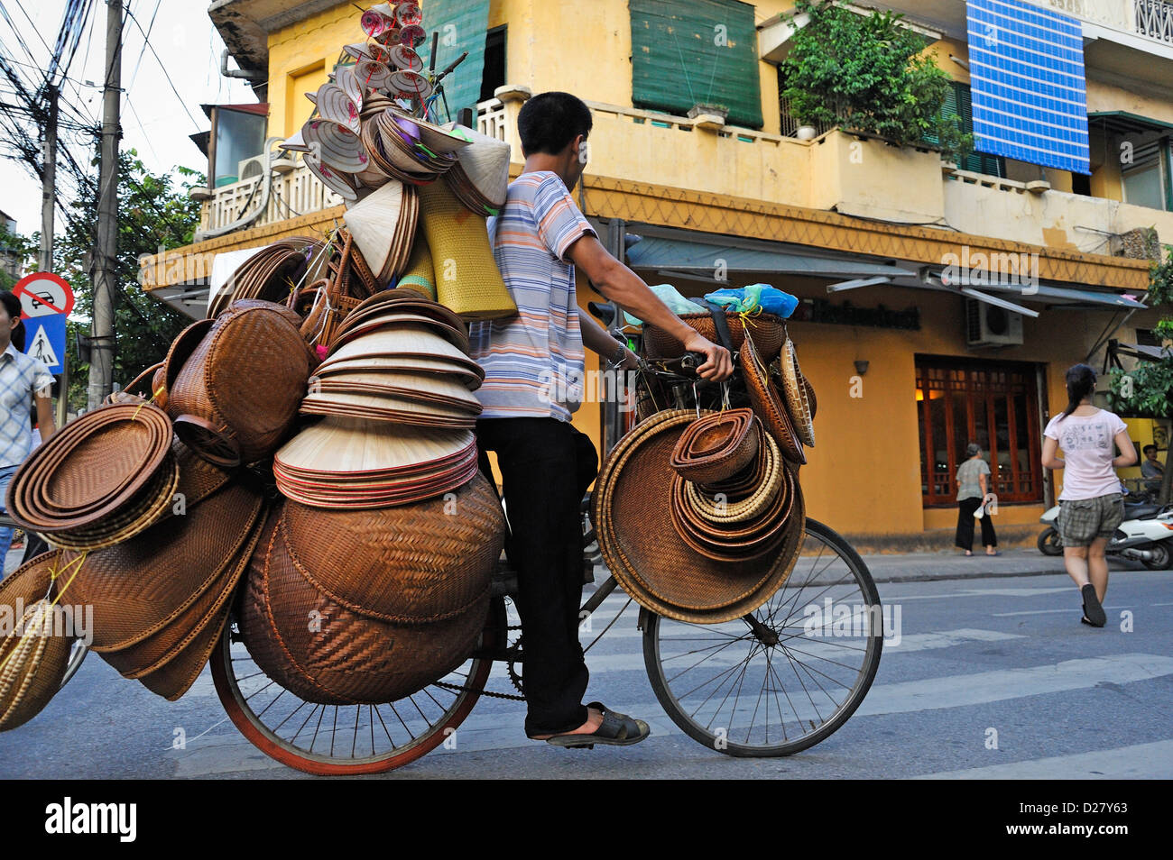 Man on a bicycle selling straw bowls and hats, Hanoi, Vietnam - Stock Image