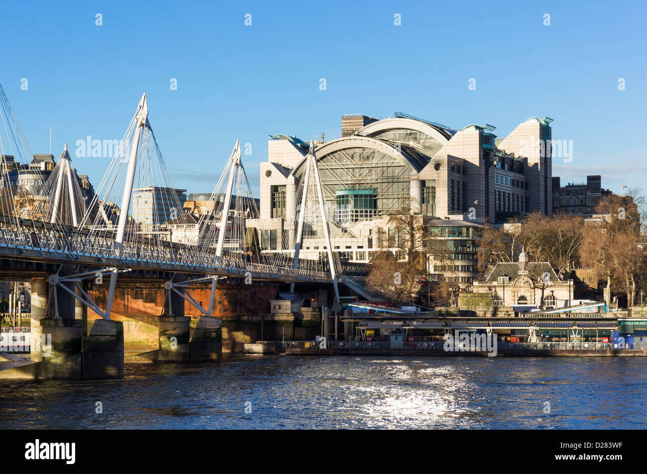 The Embankment Place building housing Charing Cross station, with Hungerford Bridge across The Thames, London, UK - Stock Image