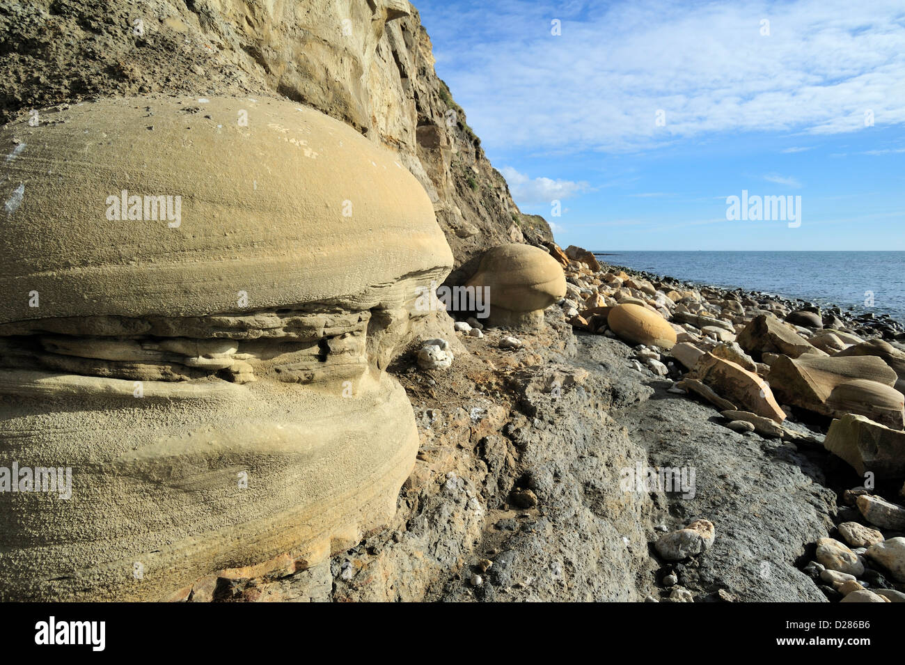 Rounded nodules on beach at Osmington Mills come from the Bencliff Grit Formation, Jurassic Coast, Dorset, southern - Stock Image