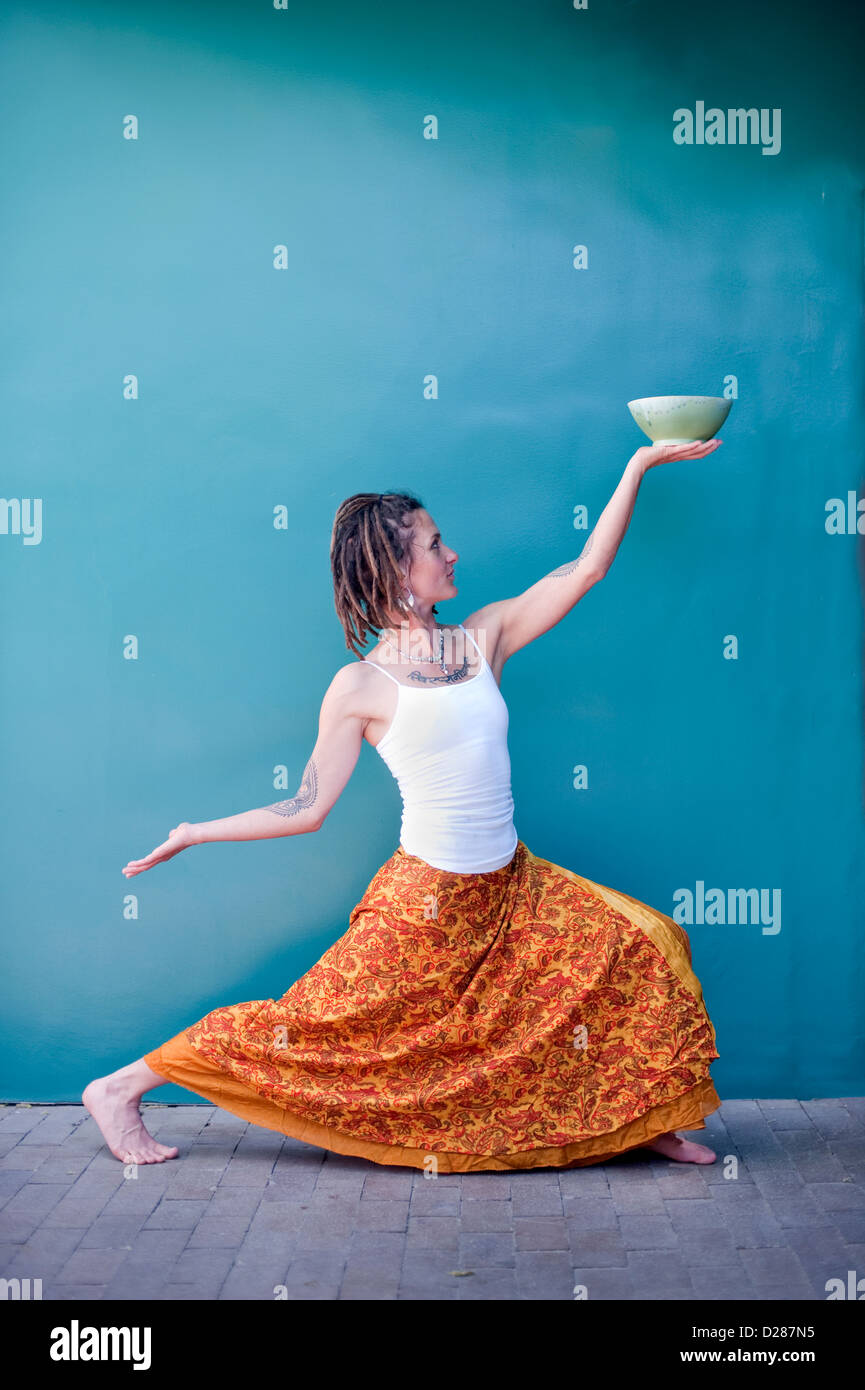 Unique woman in a dancing yoga posture offering up a beautiful ceramic bowl against the backdrop of a blue wall. - Stock Image
