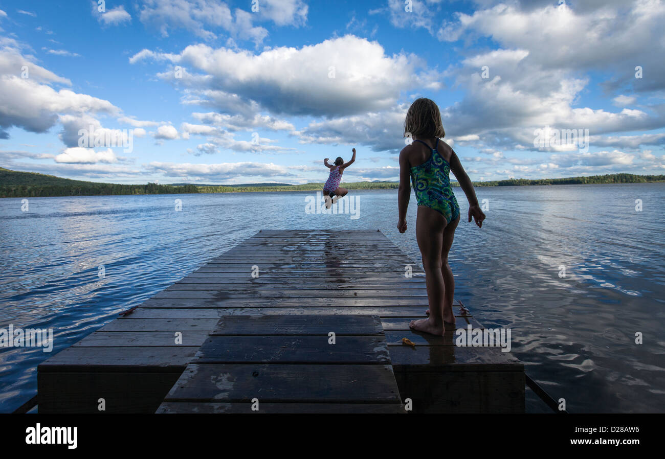 A young girl jumps off of a dock on a lake in Northern Maine, while her sister watches. Stock Photo