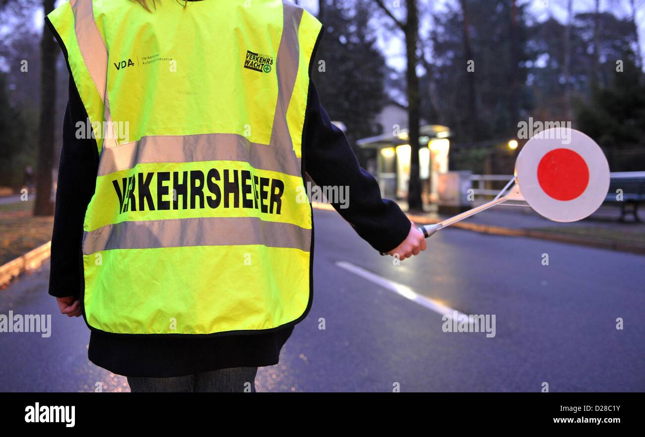 School crossing guard holds a signalling disc in her hand indicating for  the traffic to stop
