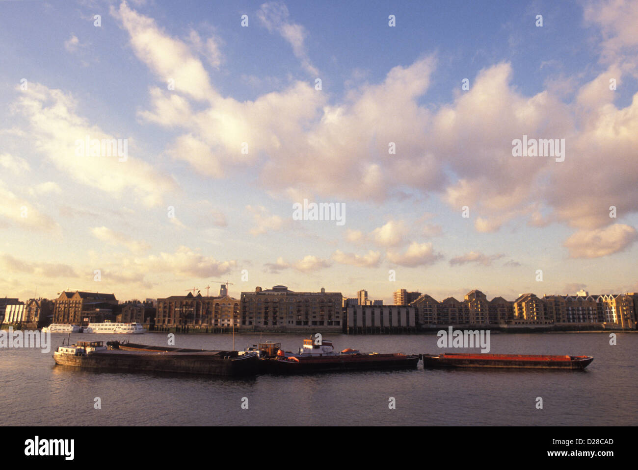 Barges on London's Thames with the shore of Wapping behind. 1989. - Stock Image