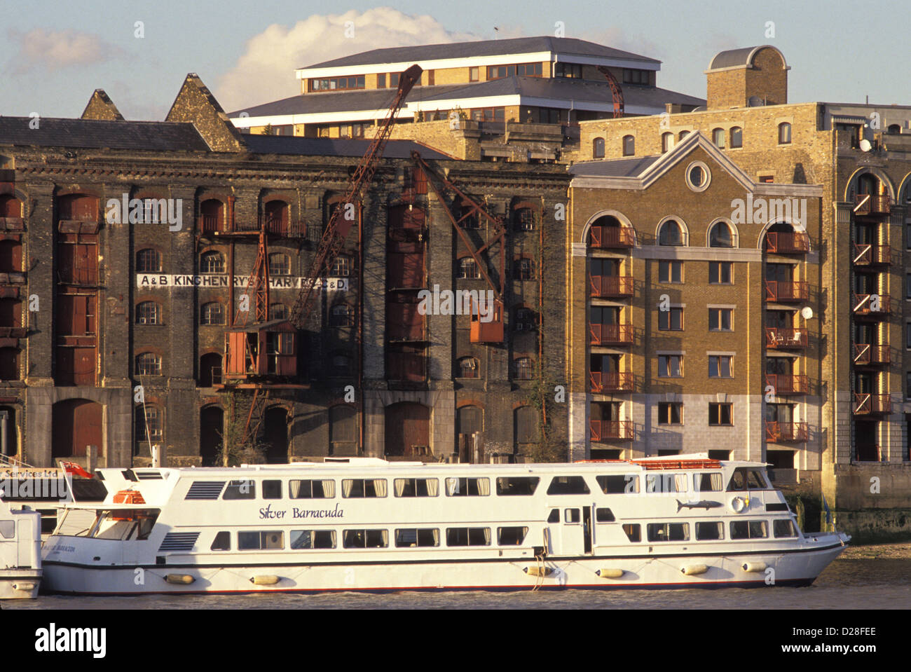 London: a river cruiser moored by warehouses and new-build flats at Wapping in the 1980s. 1989. - Stock Image