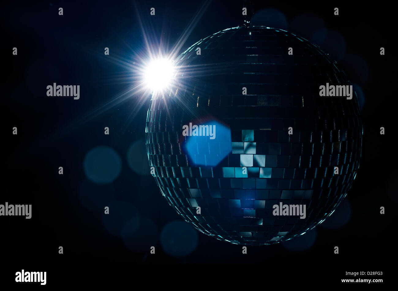A disco ball with light flare and blurry lights on background. A nightlife image to be used as example on party - Stock Image