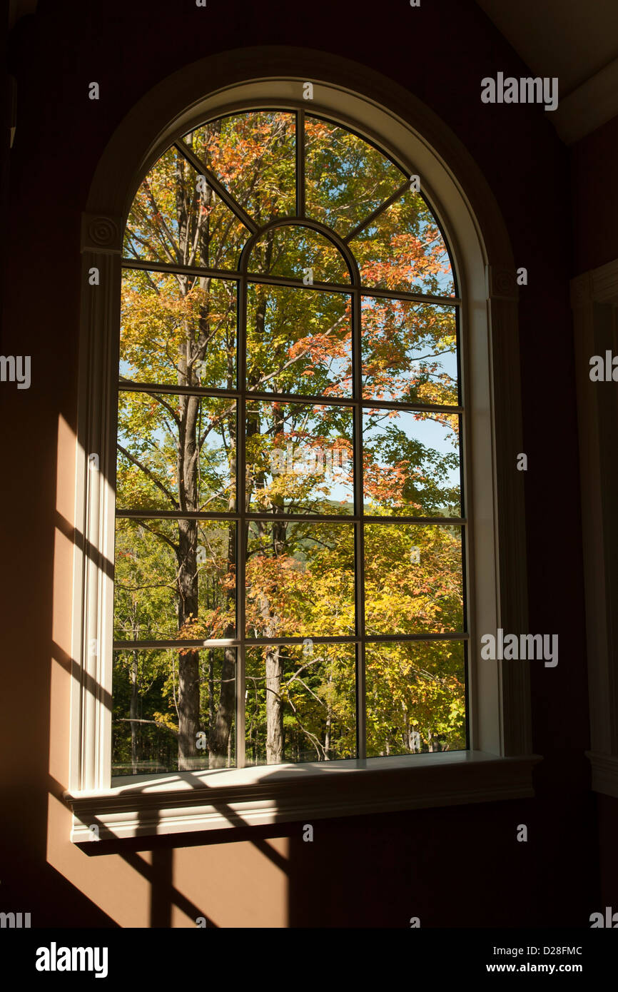 An upscale home has beautiful view of New England woods in fall. - Stock Image