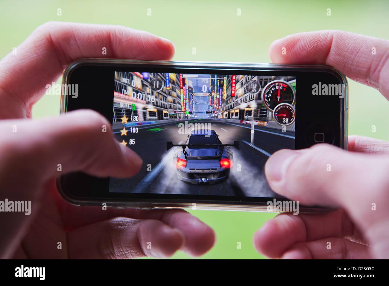 Playing car racing game on smartphone. - Stock Image