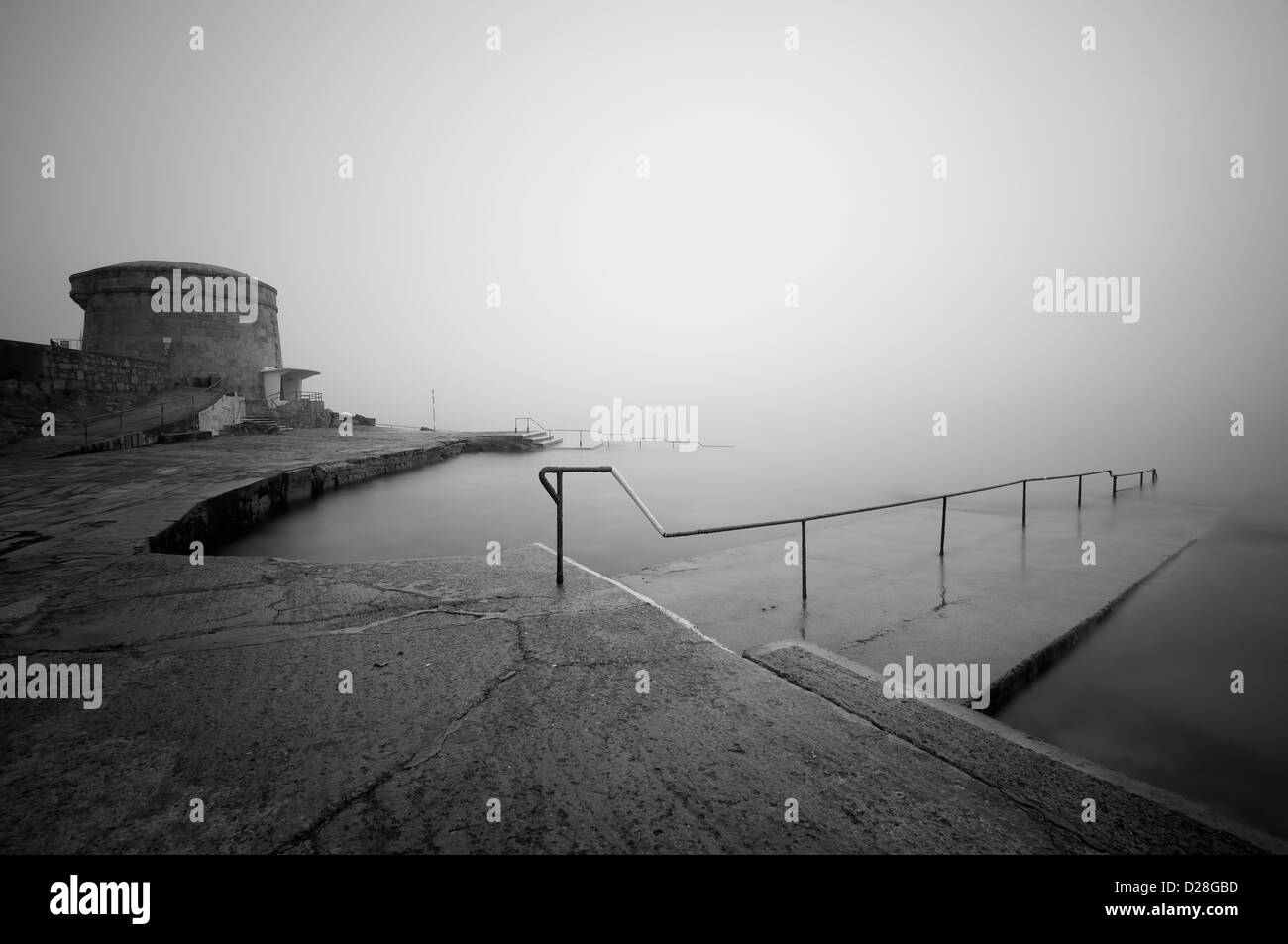 A peaceful bathing place at Martello tower early in the morning , Seapoint, Co. Dublin, Ireland in black and white. - Stock Image