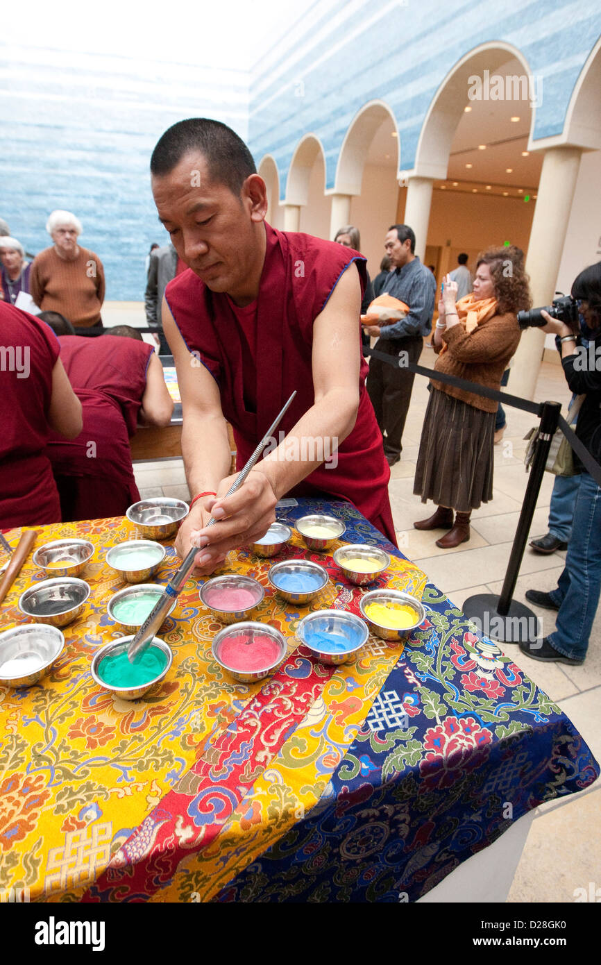 Tibetan Buddhist monks from the Drepung Loseling Monastery, construct an intricate, highly patterned large-scale - Stock Image