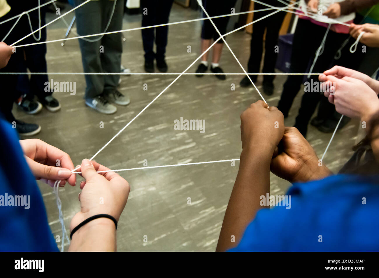 School children play a game that demonstrates their interconnectedness - Stock Image