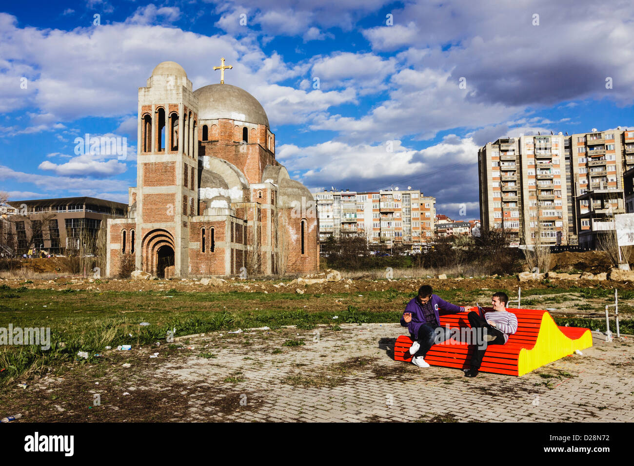 Students sitting on a bench at Pristina campus by the unfinished Serbian Orthodox Temple of Saint Saviour. Pristina, - Stock Image