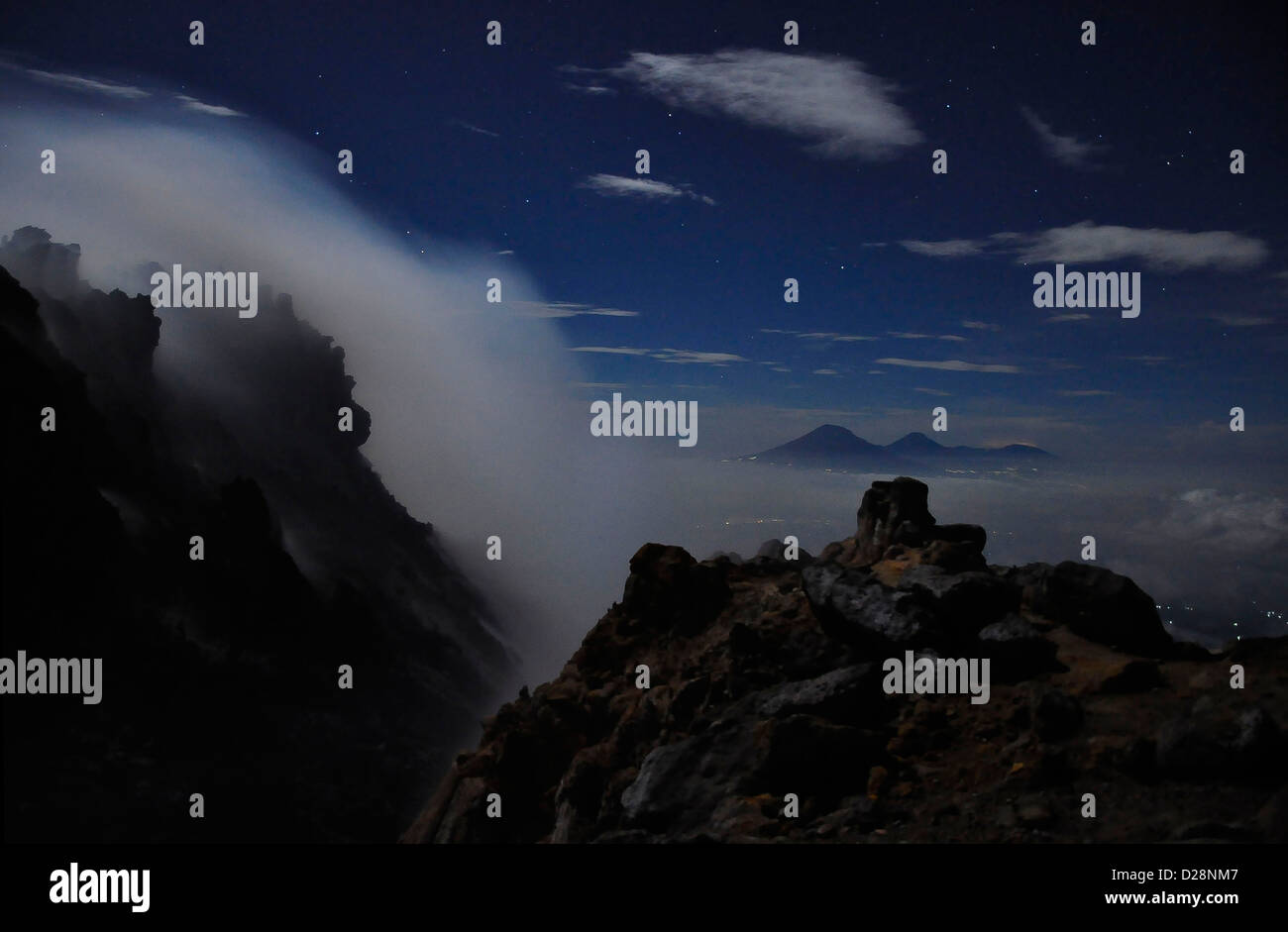 night view of the volcanic smoke on the summit of Mount Merapi to the Merbabu volcano, Central Java, Indonesia - Stock Image