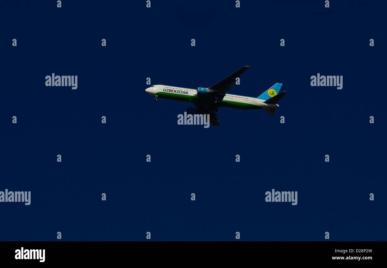 An Uzbekistan airways airplane in the air. - Stock Image