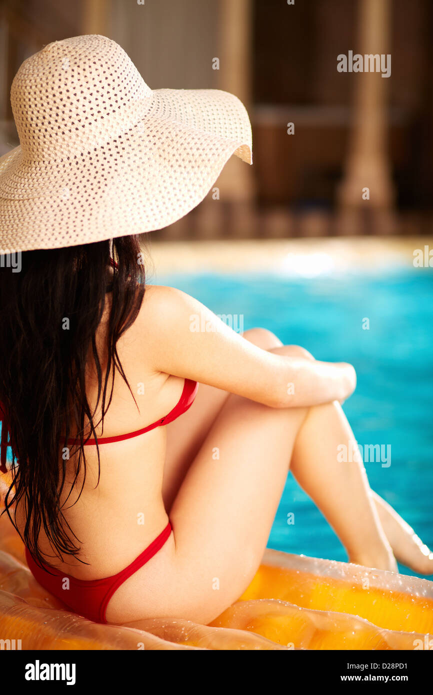 Back view of lovely woman in bikini and hat sitting on mattress - Stock Image