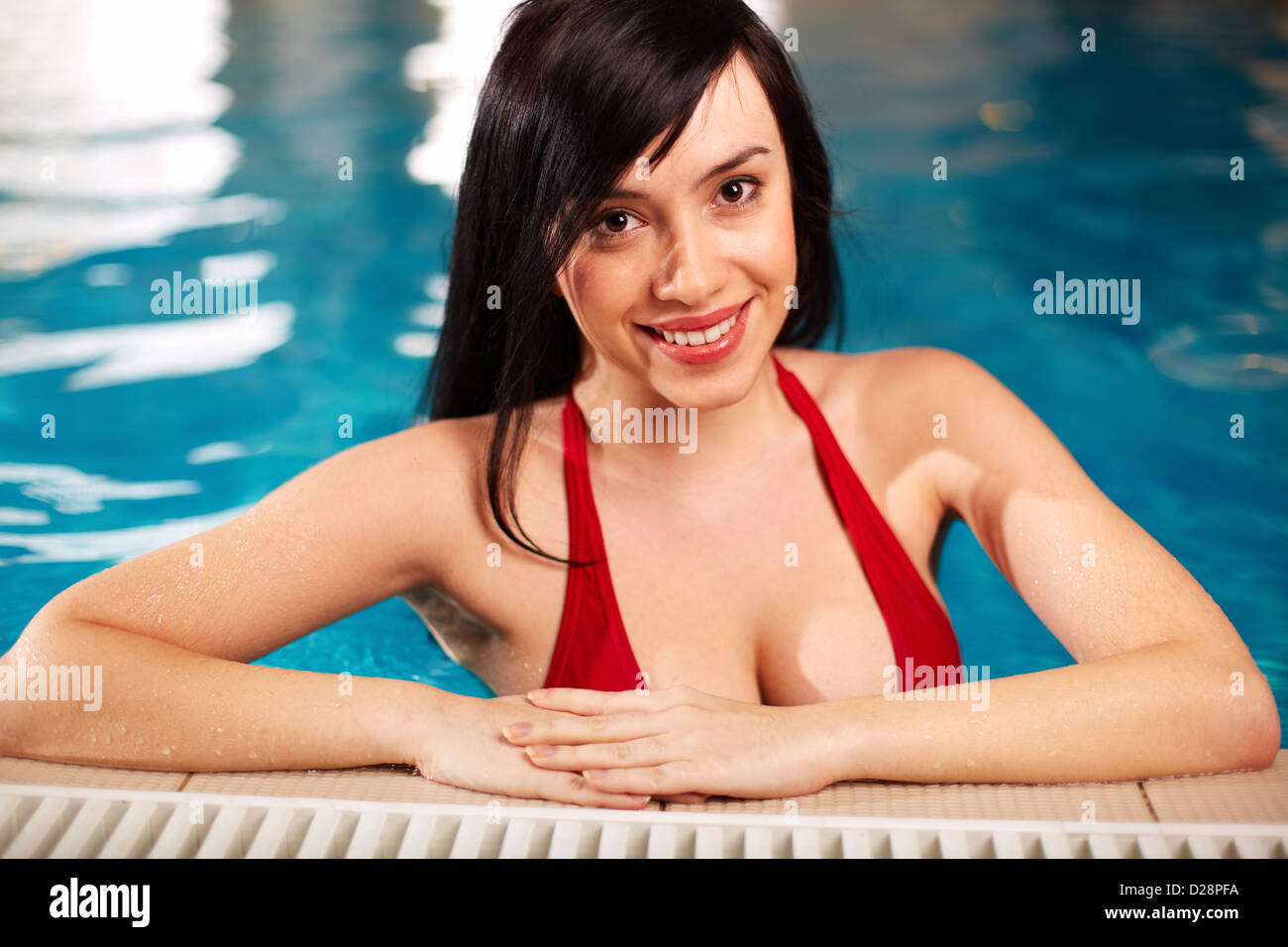 Portrait of lovely woman in bikini looking at camera in swimming pool - Stock Image