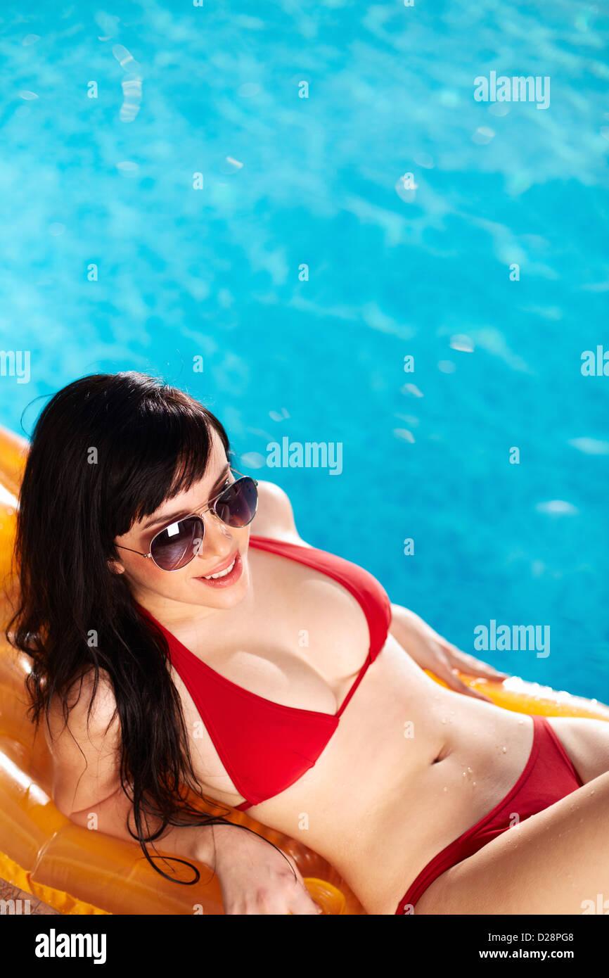 Lovely woman in bikini and sunglasses lying on mattress - Stock Image