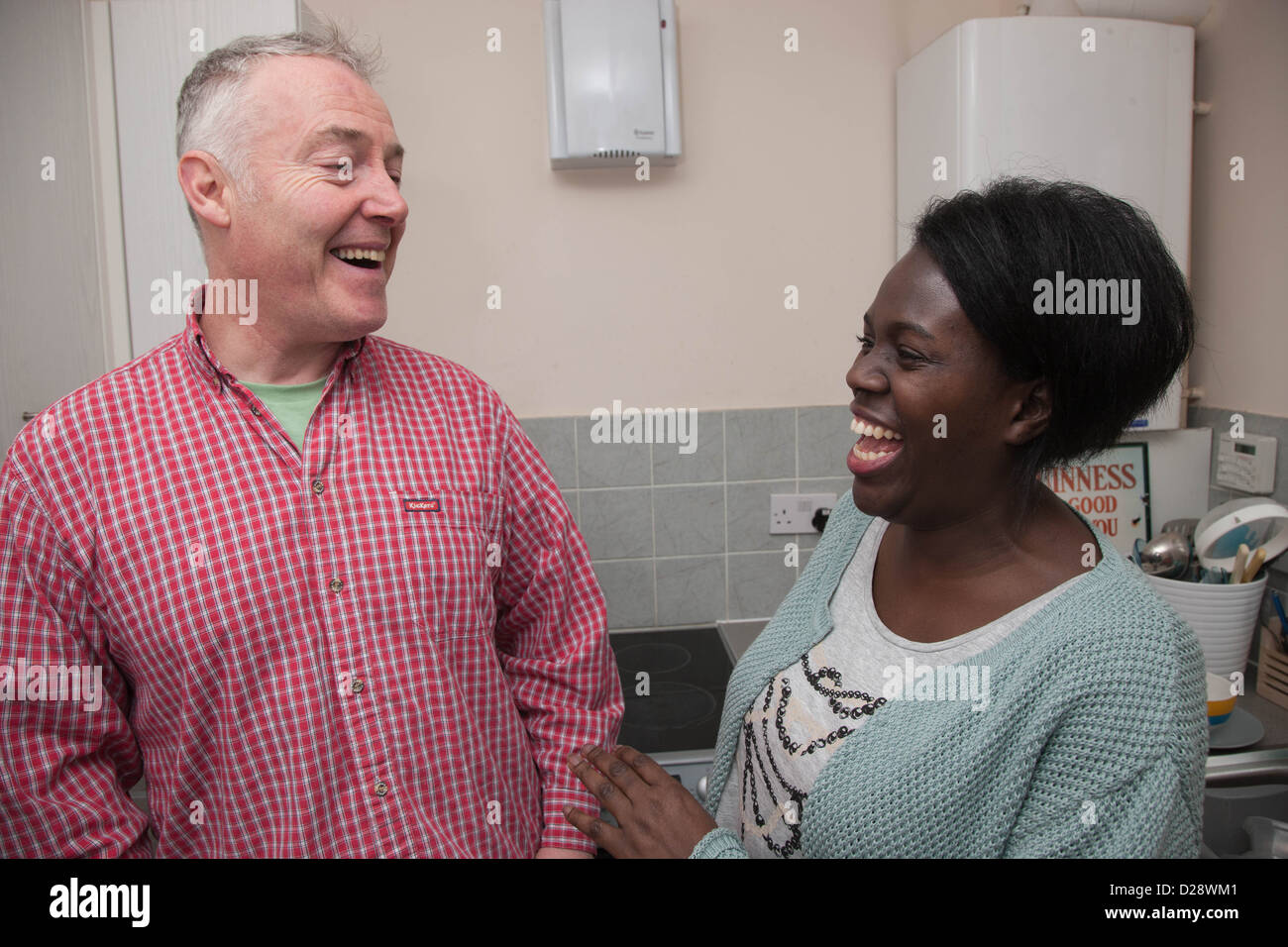 Couple having a joke in a kitchen. - Stock Image