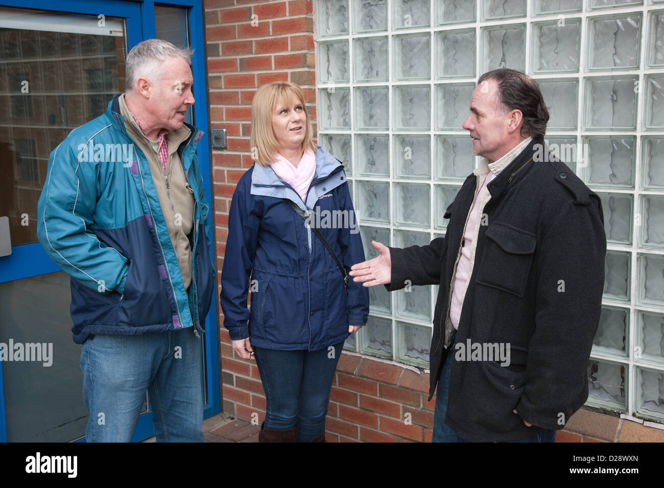 Tenants and housing officer at entrance to flats. - Stock Image