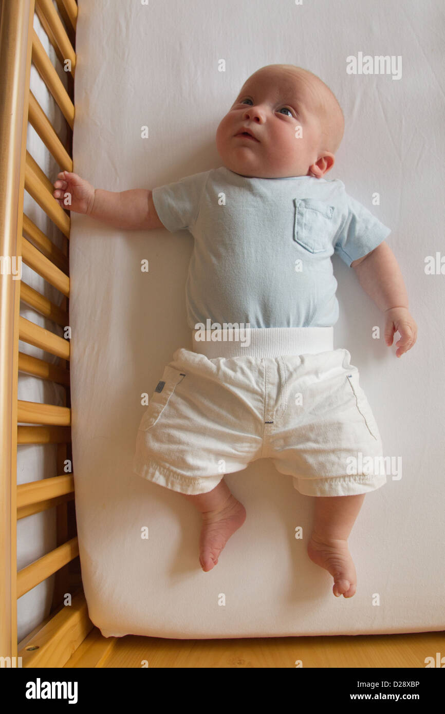 Baby in cot. - Stock Image