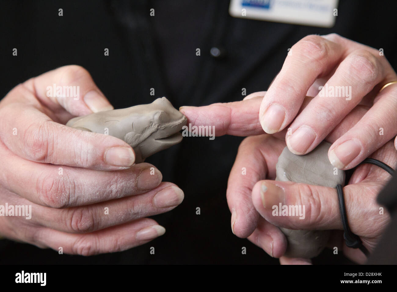 Visually impaired people with carers on outing to Denby Pottery. Touching clay frog. - Stock Image