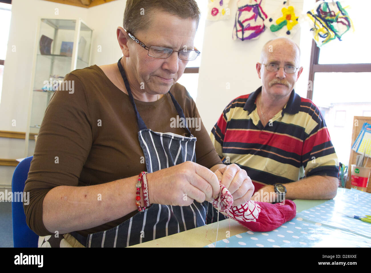 Felt making class for people with a visual impairment - untying felt from a roll. - Stock Image