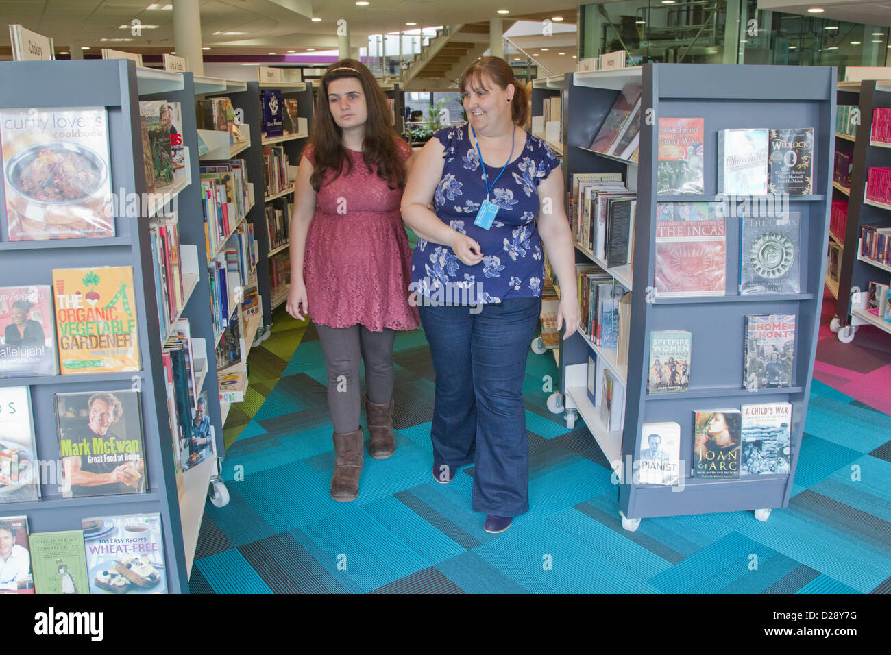 Out reach worker walking through book shelves with visually impaired woman - Stock Image