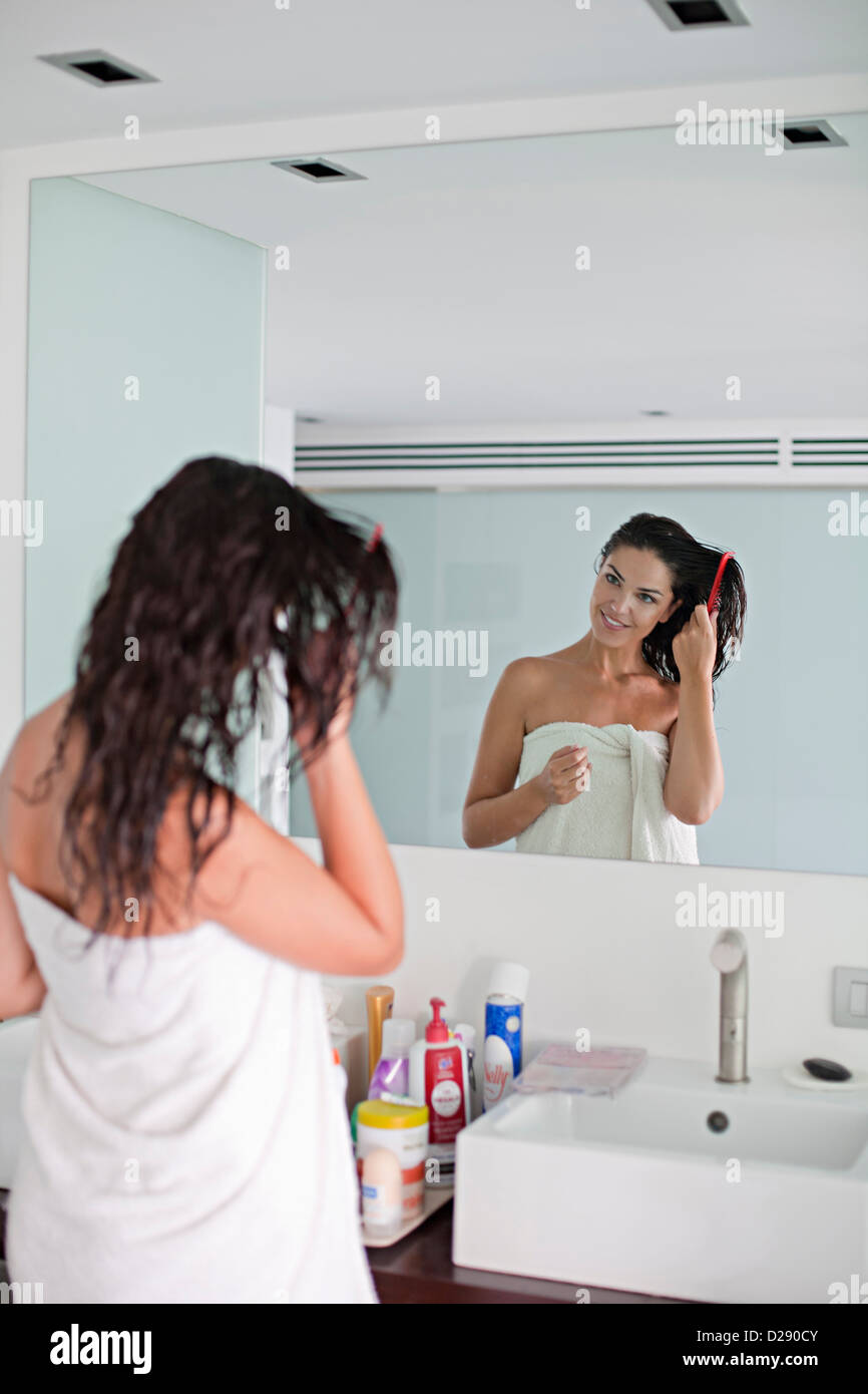 Brunette woman brushing her hair in front of the mirror Stock Photo