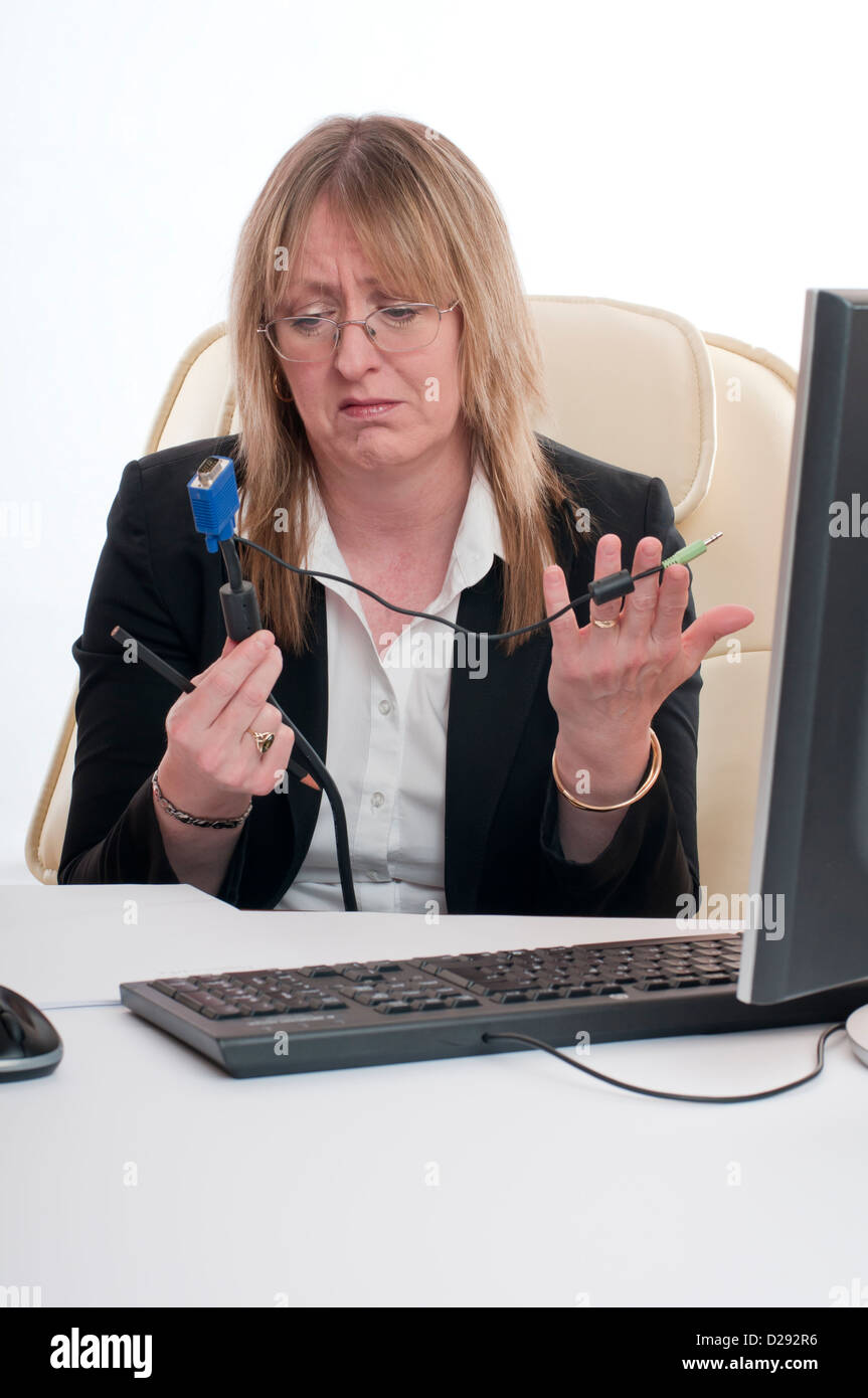 very confused woman holding a unplugged cable from her PC whilst working in the office - Stock Image