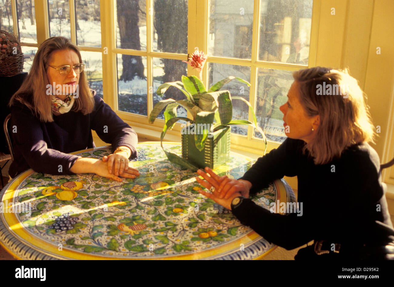 Two Friends (30'S) Converse At Table - Stock Image