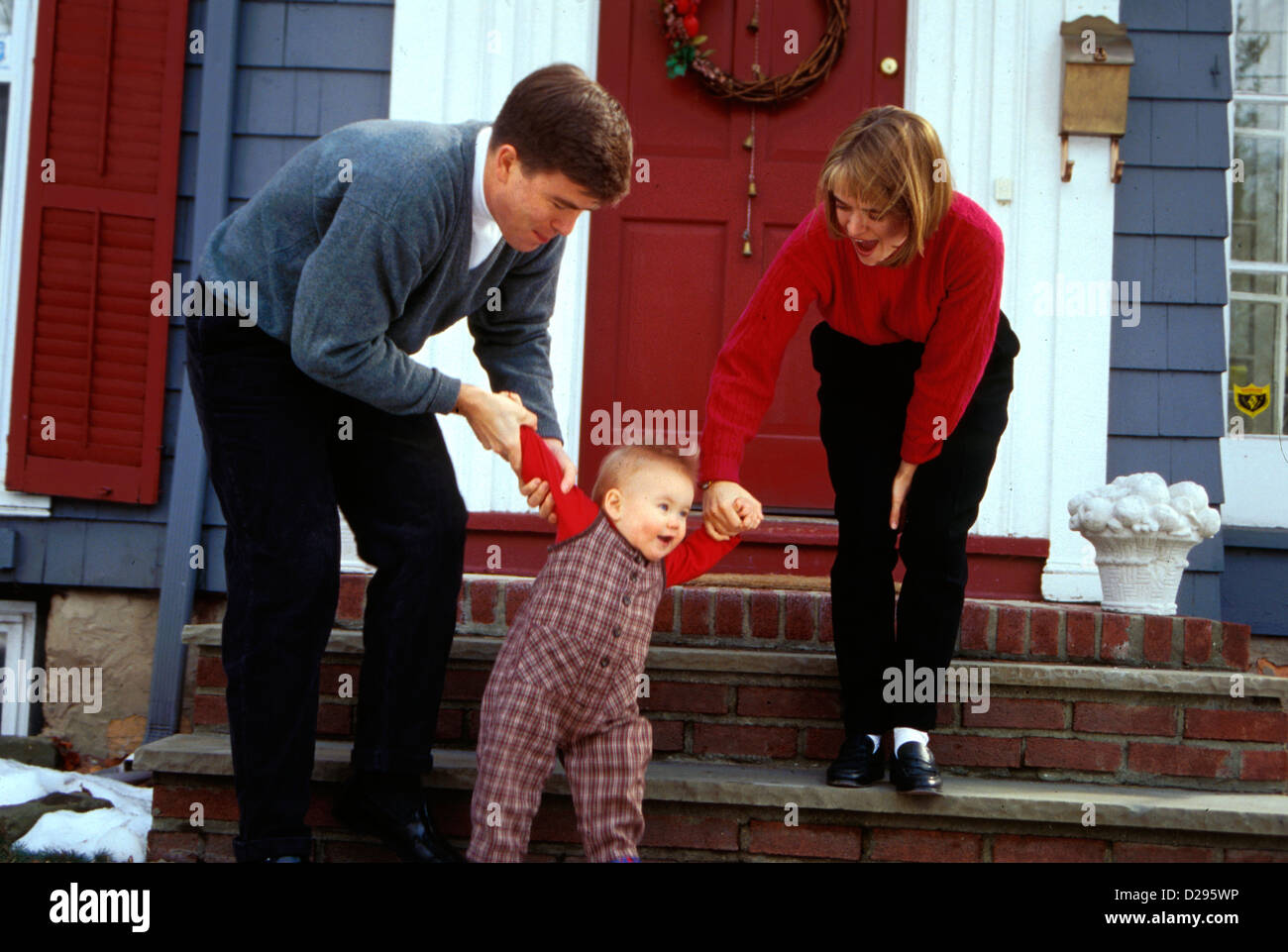 Parents In Their 30'S Walking Down Steps With One Year Old Baby - Stock Image