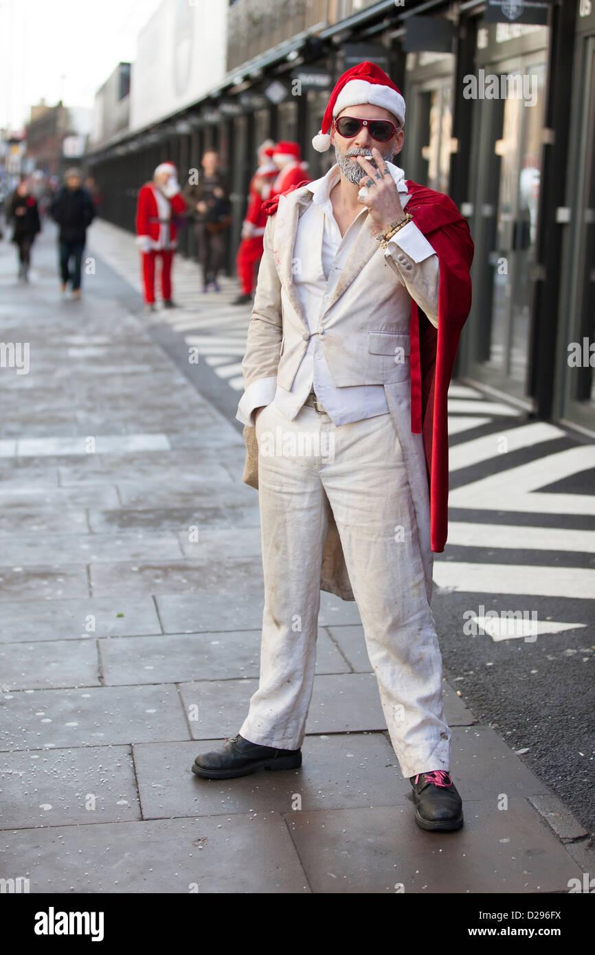 A reveller at Santacon, London, December 2012, pauses for a cigarette break. - Stock Image