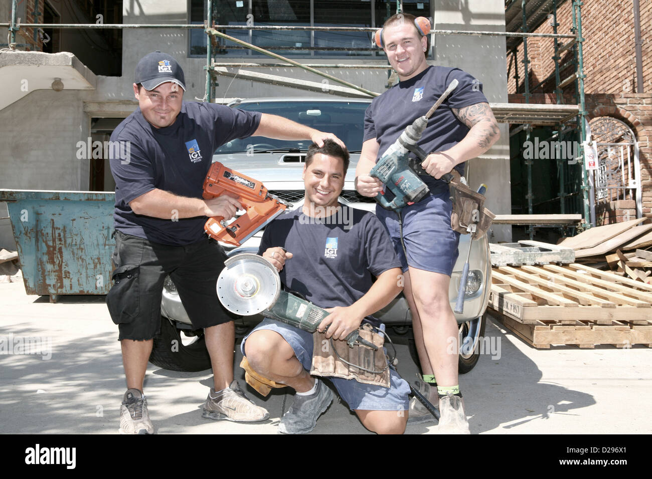 Tradesmen being funny and  posing with power tools for a photograph. - Stock Image