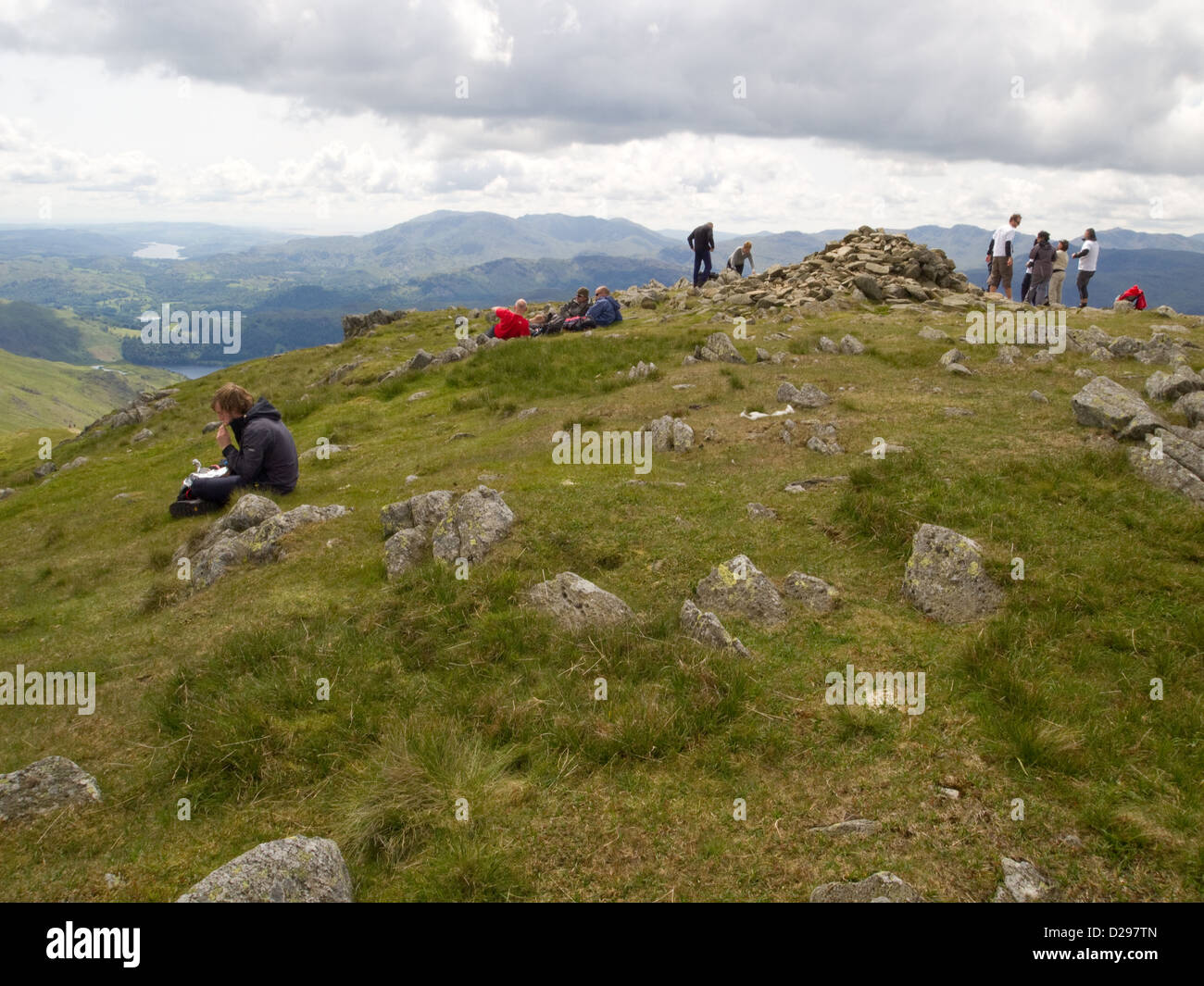 Walkers taking a well earned rest on the summit of Great Rigg in the Lake District - Stock Image