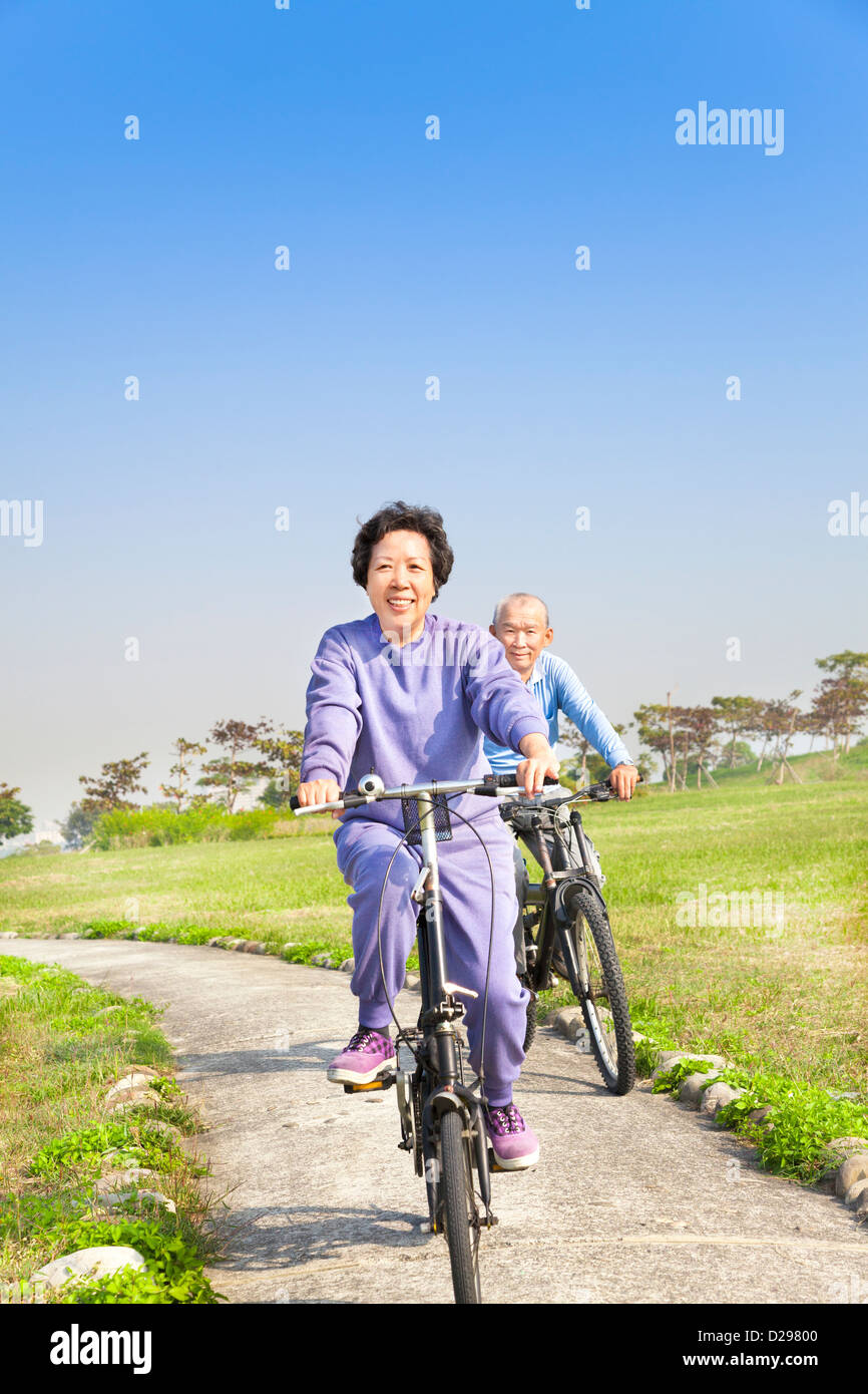 asian seniors couple biking in the park - Stock Image