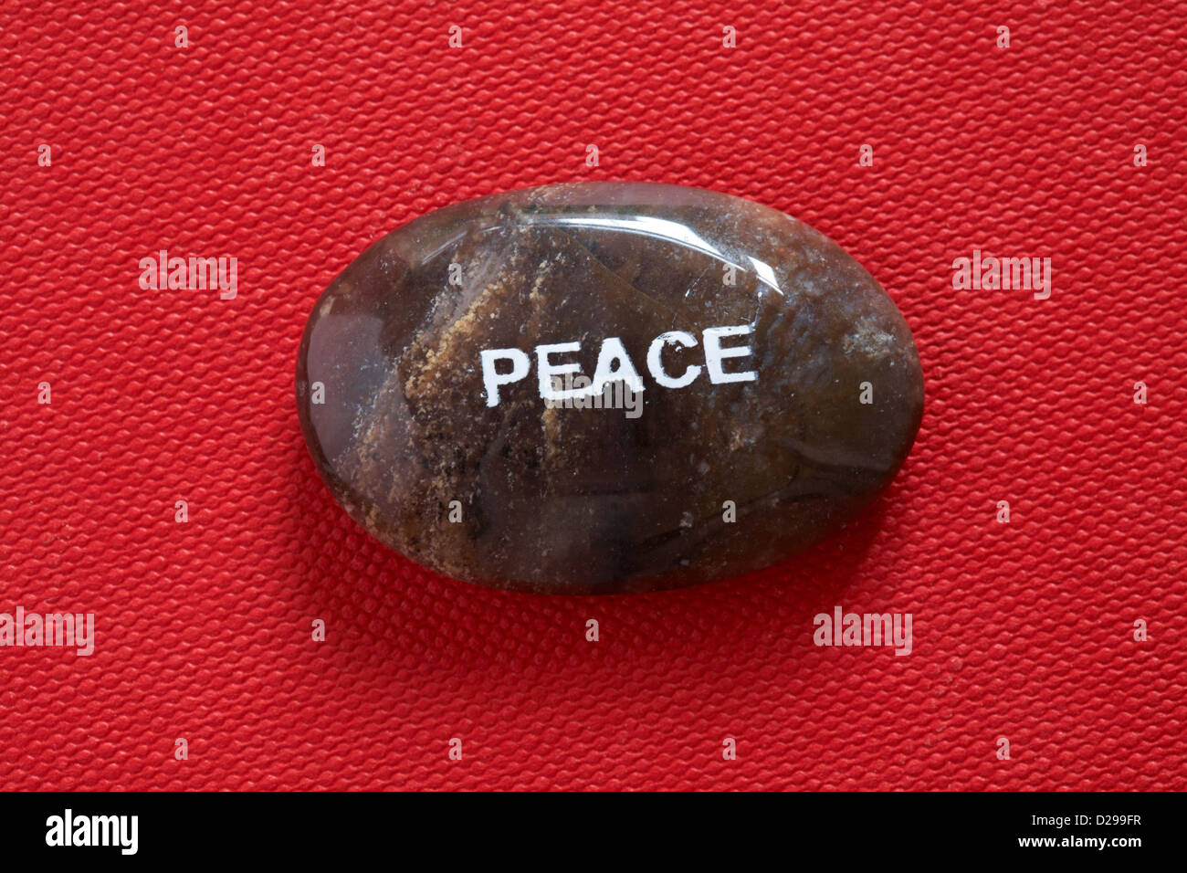 Fair Trade sentiment pebbles - Peace pebble isolated on red background - Stock Image