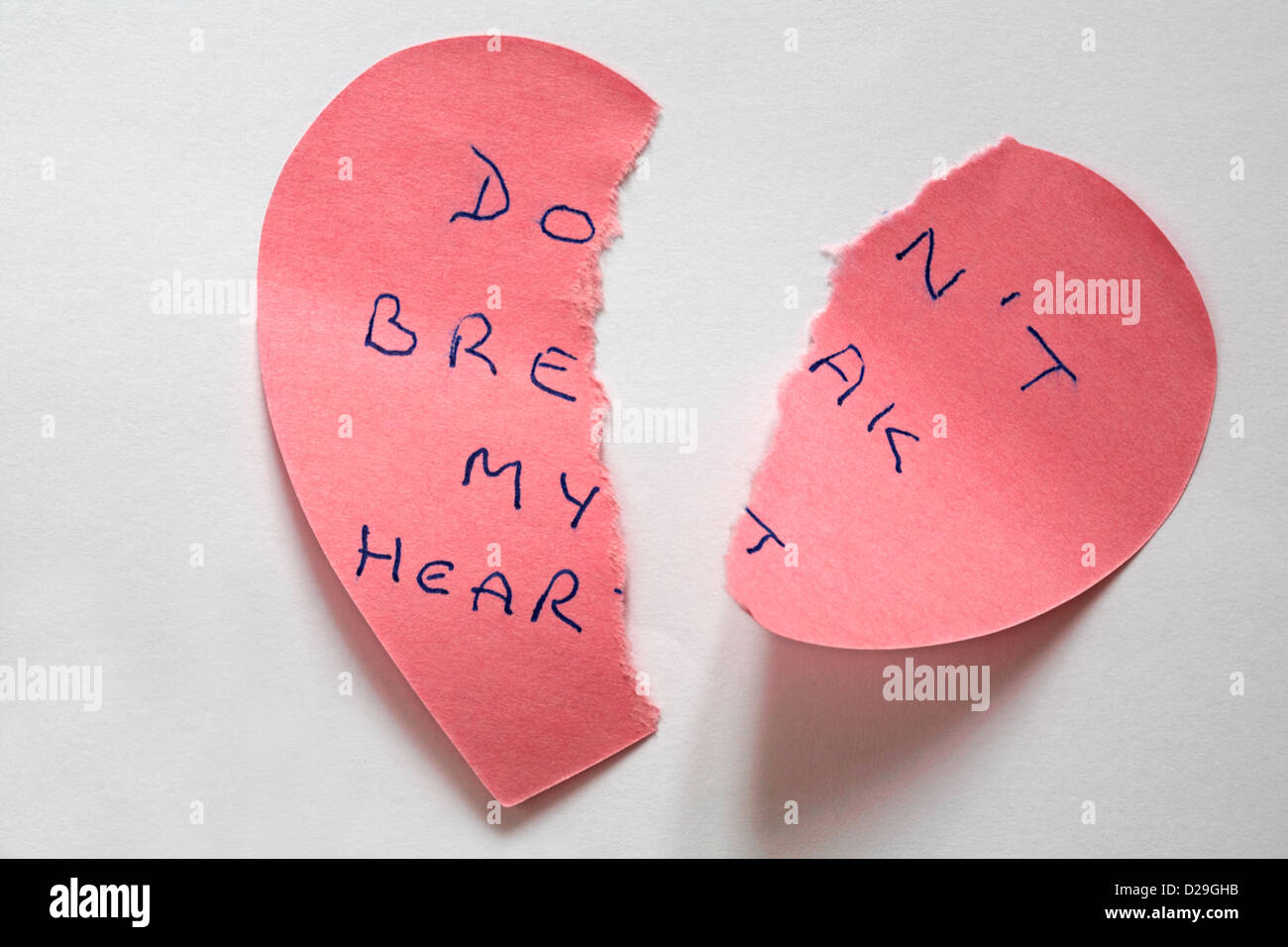 heartbroken - don't break my heart message written on torn up pink heart shaped post it note isolated on white - Stock Image
