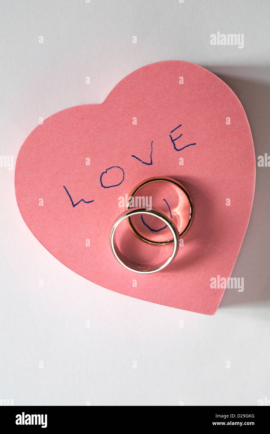 Love U message written on pink heart shaped post it pad with two ...