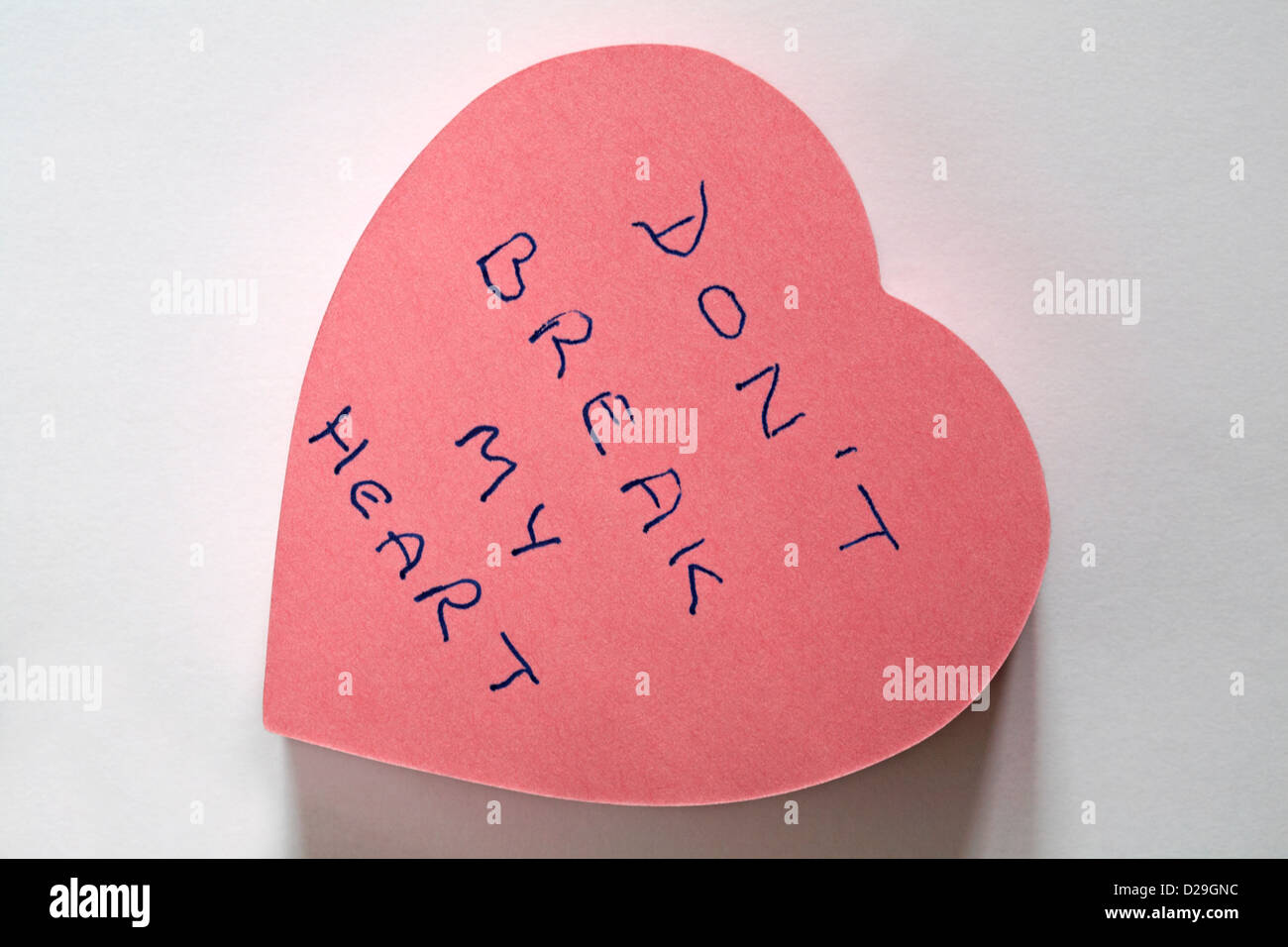 don't break my heart message written on pink heart shaped post it note pad isolated on white background - Stock Image