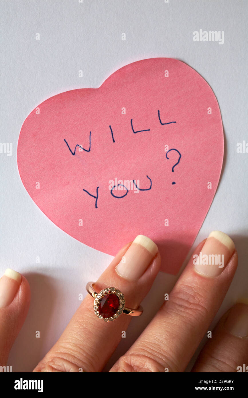 will you? message written on pink heart shaped post it note with fingers putting on engagement ring - ready for - Stock Image